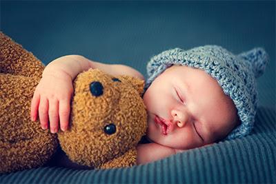 Sleeping baby holding a teddy bear