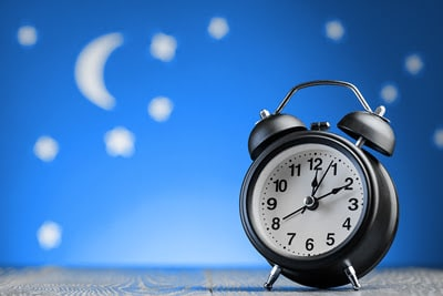 Round alarm clock in a blue background with moon and stars